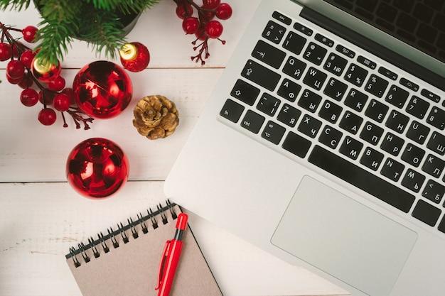 크리스마스 장식으로 테이블에 메모장 및 컴퓨터를 엽니 다