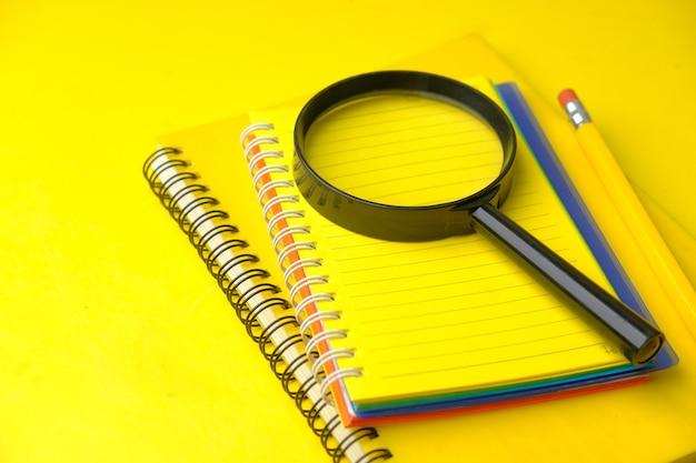 노란색 표면에 열려있는 메모장 및 돋보기