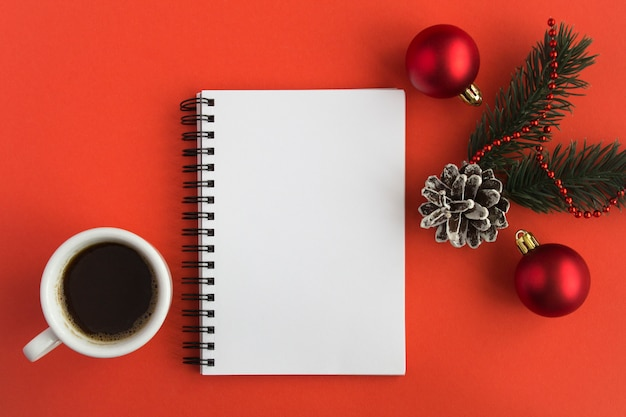 Open notepad, black coffee in the white cup and christmas composition on the  red  surface. copy space. top view.