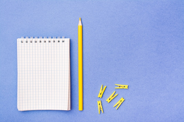 Open notepad in a cage on a spiral, yellow pencil and clamps on a blue
