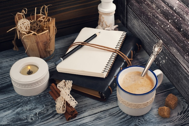 Open notepad, candle, pencil and coffee