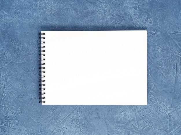 The open notepad  clean white page on aged dark blue stone table, top view