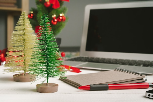 Open notepad and computer on table with christmas decor