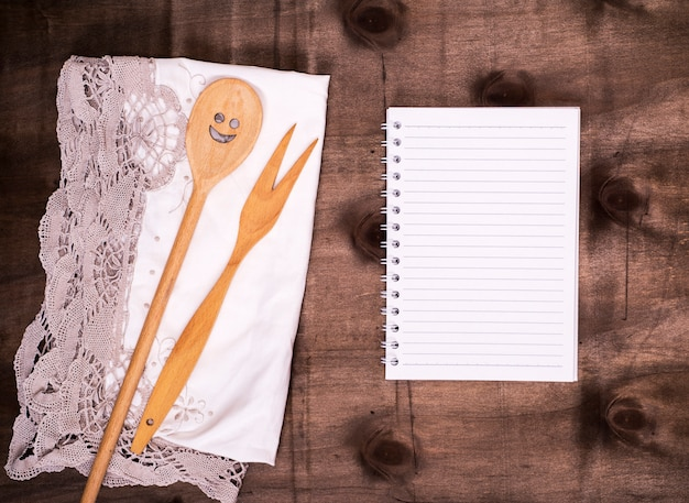 Open notepad in a line and a wooden spoon with a fork