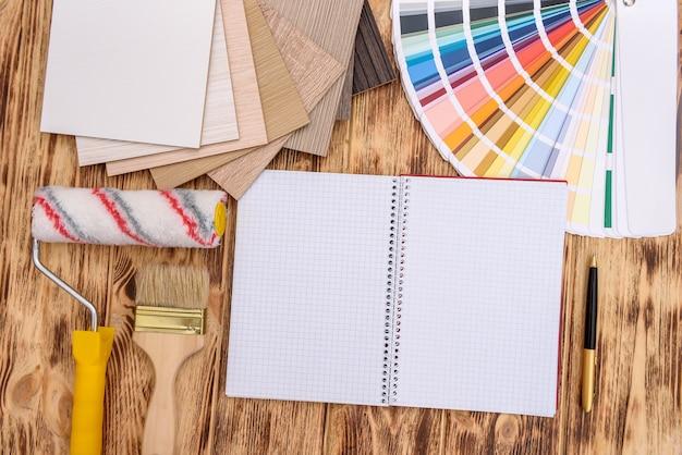 Открытый блокнот на столе с образцом цвета и дерева