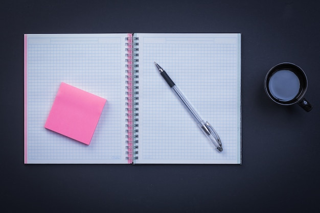 Open notepad pen sticky note and cup of coffee on black background education concept