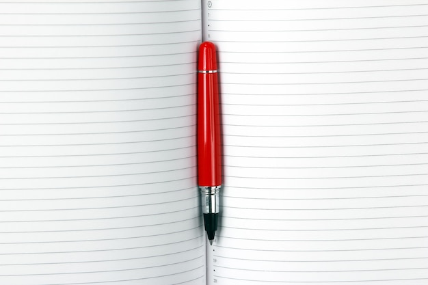 Open notepad and red pen closeup