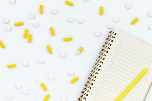 Open notepad and scattered pills on white table