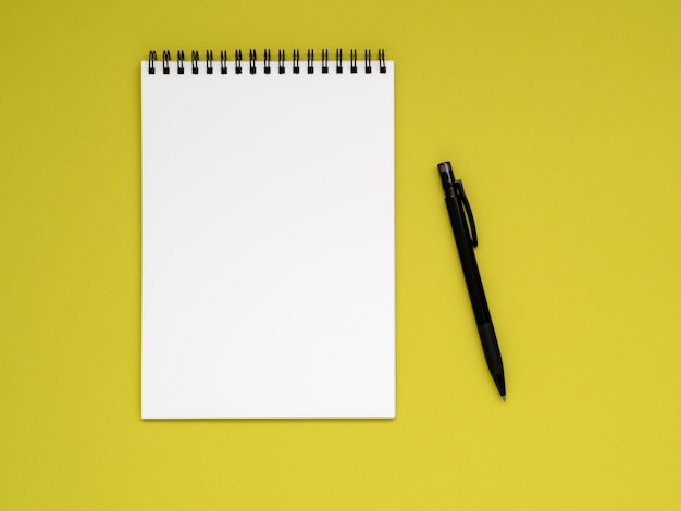 Open notepad on the spiral with a clean white page and pencil on a bright yellow background color
