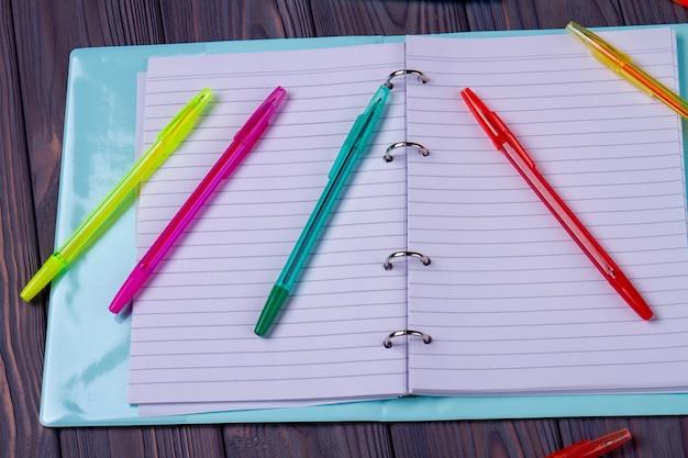 空白のページと多くのペンでメモ帳を開きます。灰色の机の背景。