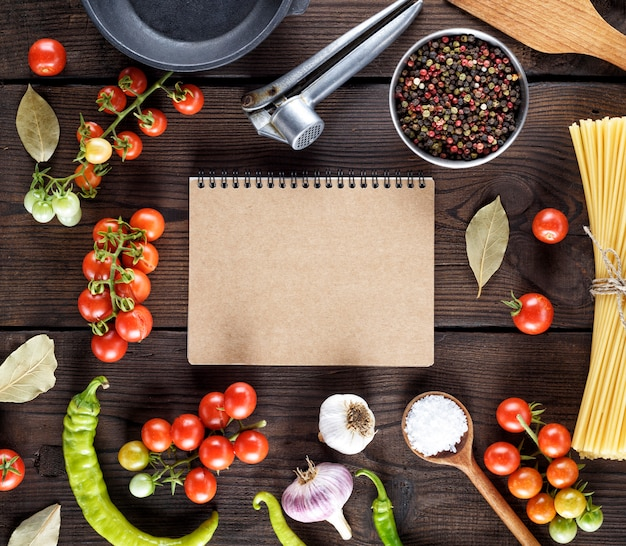 Open notepad with brown sheets and ingredients for cooking pasta