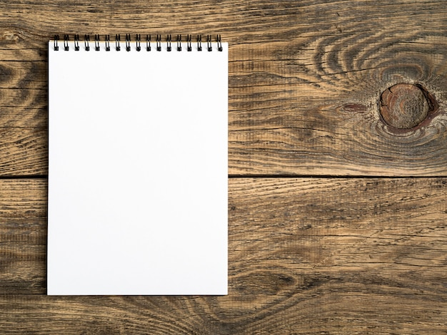 Open notepad with a clean white page on wooden table, top view
