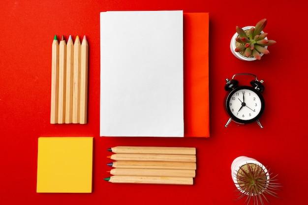 Открытый блокнот с цветными карандашами и цветочными горшками на красном фоне, вид сверху