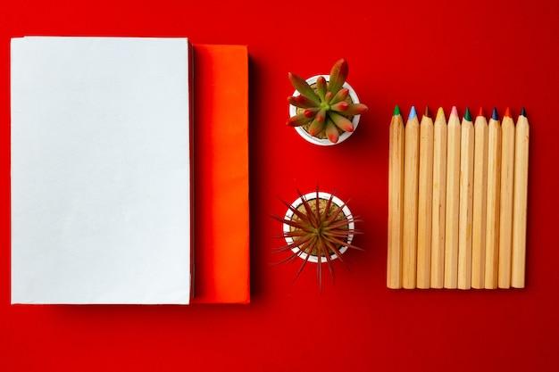 Открытый блокнот с цветными карандашами и цветочными горшками на красном