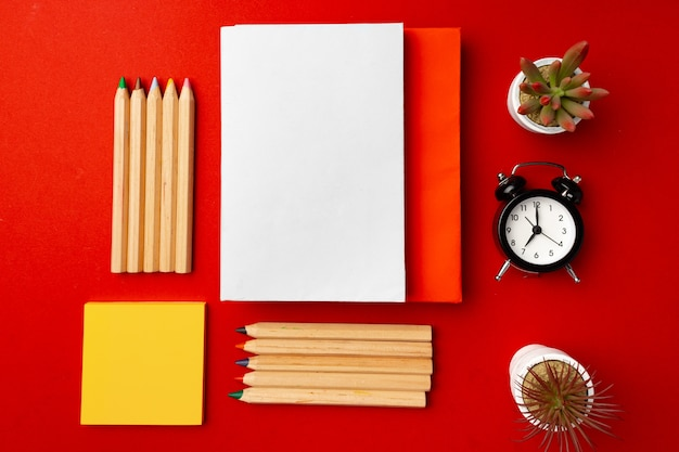 Open notepad with color pencils and flower pots on red background top view