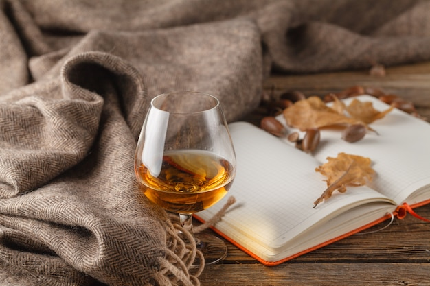 Open notepad with empty white pages and warm scarf on wooden table with autumn leaves, top view