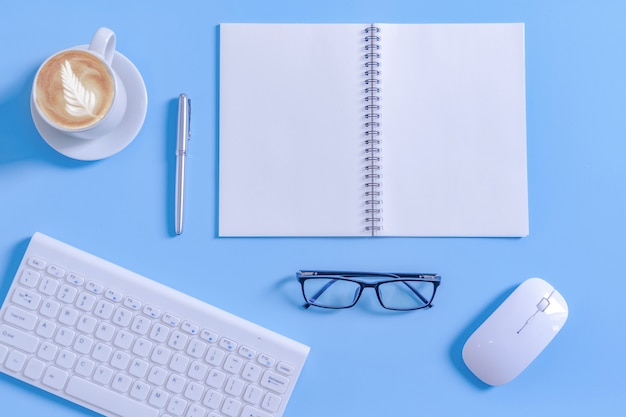 オフィス機器と作業机の上のラテコーヒーカップでメモ帳を開きます。