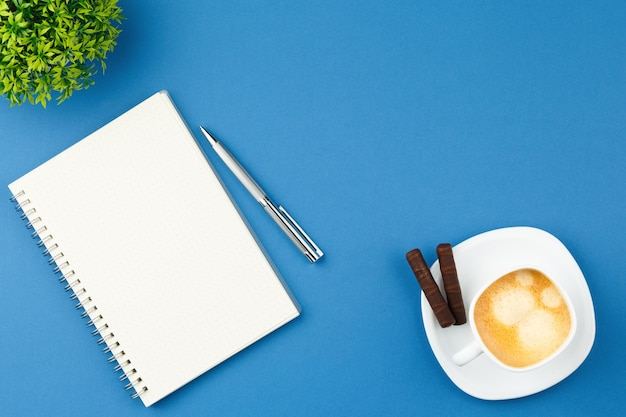 Open notepad with pen cup of coffee and plant