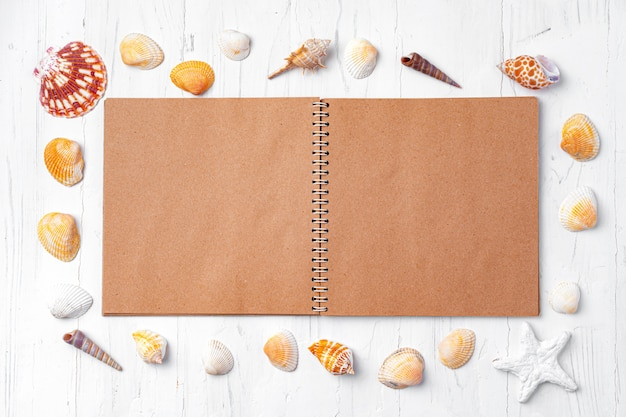 Open notepad with sea shells on white wood