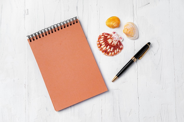 Open notepad with sea shells on white wooden