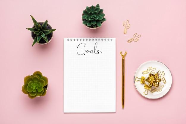 텍스트 목표 2022 목표, 다육 식물, 분홍색 배경에 황금 펜, 테이블 비즈니스, 계획, 교육 개념에 나선형 노트북이 있는 메모장 열기