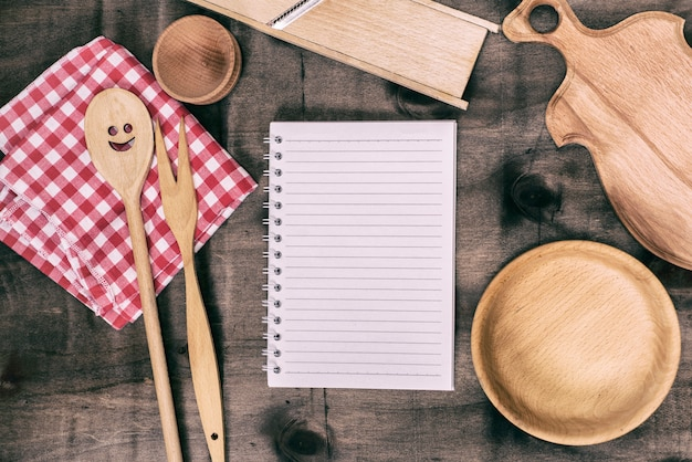 Open notepad with wooden kitchen objects