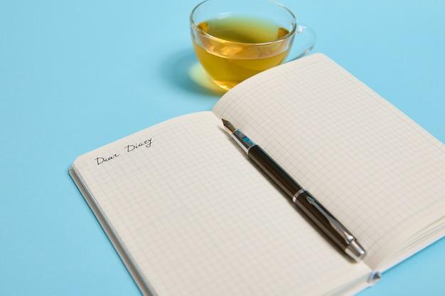 Dear diary라는 단어가 있는 메모장을 열고 텍스트 복사 공간이 있는 파란색 배경의 찻잔 옆에 잉크 펜