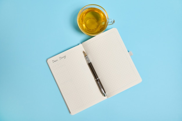 Dear diary라는 단어가 있는 메모장과 파란색 배경에 복사 공간이 있는 찻잔 옆에 잉크 펜을 엽니다. 높은 각도 보기, 평평한 위치.