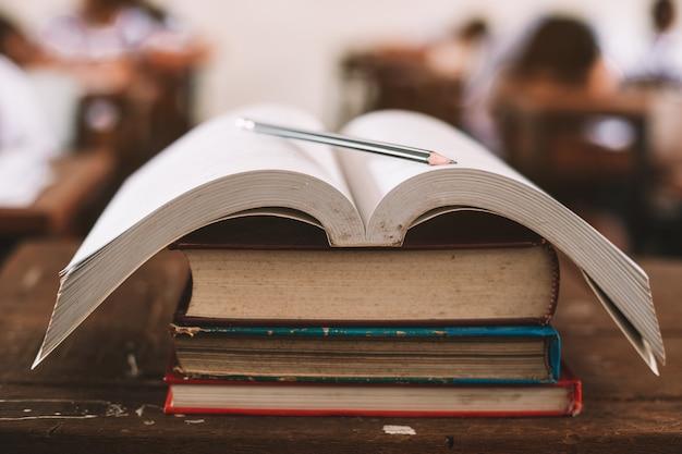 교실에서 스트레스로 시험을 보는 학생들과 함께 책상에 오래 된 책과 연필 스탠드를 엽니 다