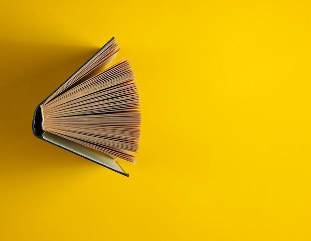 黄色に分離された古い本を開く