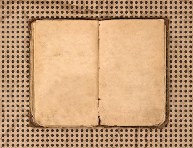 汚れた質感の水玉模様の背景の上に古い本を開く