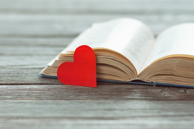 Open old book and red paper heart on wooden table