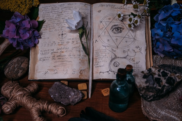 魔法の呪文、ルーン文字、黒いろうそく、魔女のテーブルにハーブのある古い本を開きます。