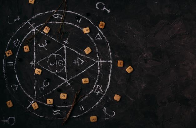Откройте старую книгу с магическими заклинаниями, рунами, черными свечами на столе ведьмы. оккультная, эзотерическая, гадательная и викка-концепция.