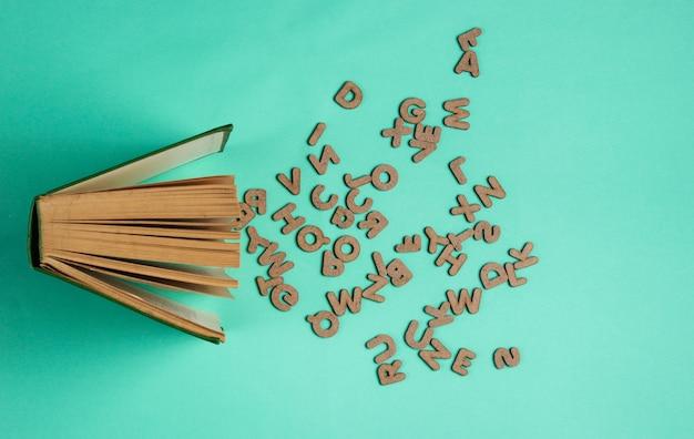 青に分離された散乱文字で古い本を開く