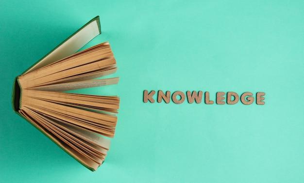 木製の文字の単語知識で古い本を開く