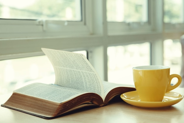 Open old book with yellow cup of coffee on the desk