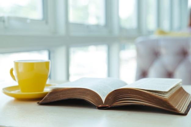 机の上に黄色いコーヒーカップで古い本を開く