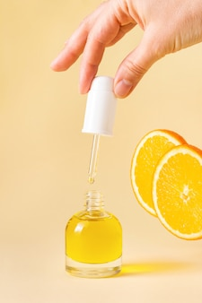 Open orange bottle with pipette in woman's hand on light yellow background