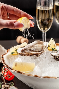 Open oysters lie on crushed ice with lemon
