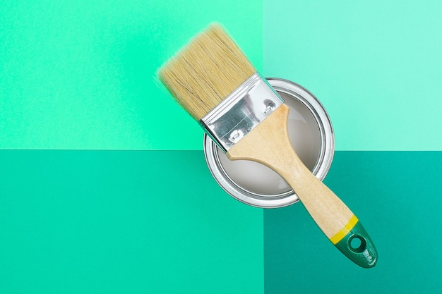 Open paint can with brush beside
