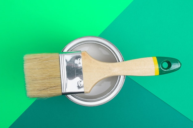 Open paint can with brush