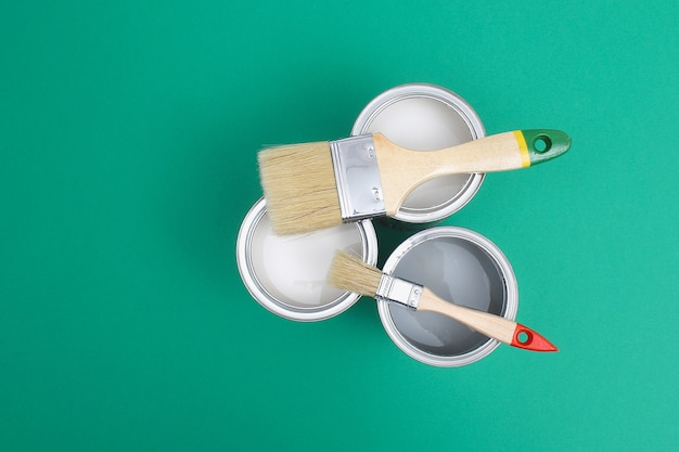 Open paint cans with brushes beside