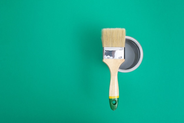 Open paint enamel cans on green turquoise palette samples.