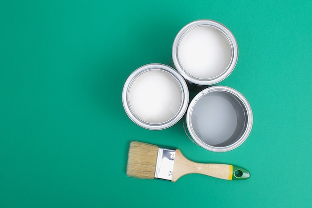 Open paint enamel cans on green turquoise palette samples