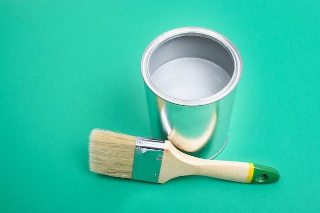Раскройте банки с эмалью краски на образцах цветовой палитры. концепция ремонта, строительства. оттенки бирюзово-зеленого.