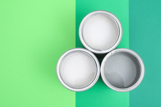 Раскройте банки с эмалью краски на образцах цветовой палитры. концепция ремонта, строительства. оттенки зеленого.