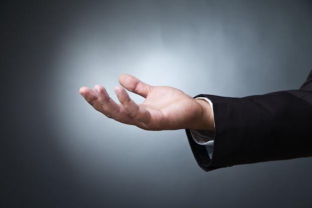 Жест рукой открытой ладони мужской руки на темном фоне