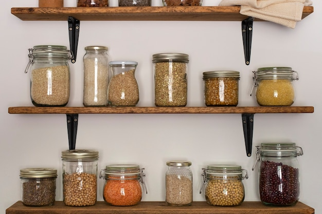 穀物やマメ科植物で満たされたガラス製の貯蔵容器を備えたオープンパントリーの木製棚有機食品