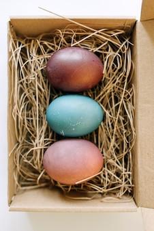 Открытая посылка с крашеными пасхальными яйцами. концептуальный праздник вид сверху фото